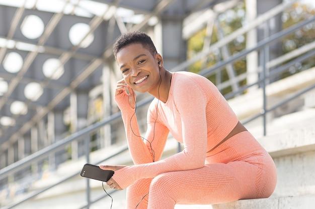 Jonge mooie vrouw in een roze sportpak glimlacht en kijkt naar de camera, luistert na de training naar muziek met een koptelefoon en een applicatie op een mobiele telefoon, tevreden