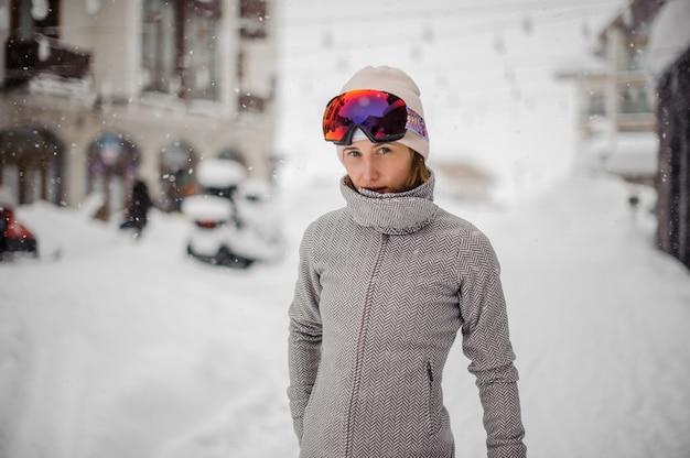 Jonge mooie vrouw in een sportmasker en een jasje die zich op sneeuwstad bevinden