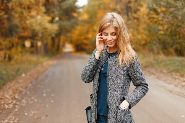 Jonge mooie vrouw in een stijlvolle herfst jas wandelen in het park