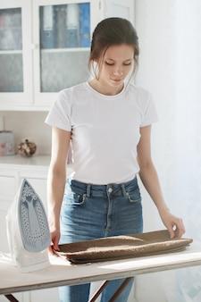 Jonge mooie vrouw in een t-shirt en spijkerbroek streelde haar ondergoed en legde haar kleren in stapels. vlakbij staat een strijkijzer, daarachter staat een wit buffet.