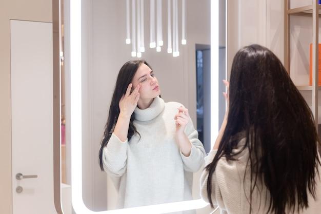 Jonge mooie vrouw in een trui in een schoonheidssalon kijkt in de spiegel, raakt haar gezicht, denkt na over de aanstaande procedures, beschouwt zichzelf