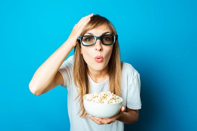 Jonge mooie vrouw in een wit t-shirt glimlacht met een bril voor 3d houdt een bord met popcorn op een blauwe achtergrond