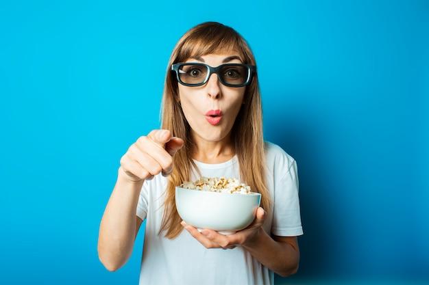 Jonge mooie vrouw in een wit t-shirt met een verbaasd gezicht en een bril voor 3d houdt een bord met popcorn op een blauwe achtergrond