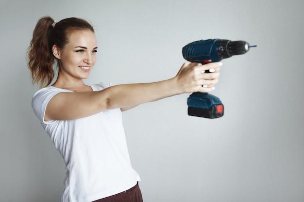 Jonge mooie vrouw in een wit t-shirt poseren met een boor in een nieuw appartement tijdens een renovatie