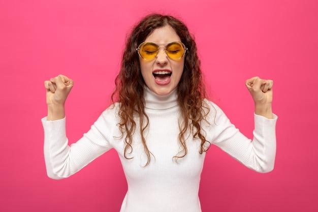 Jonge, mooie vrouw in een witte coltrui met een gele bril die vuisten opheft en schreeuwt met een geïrriteerde uitdrukking die op roze staat
