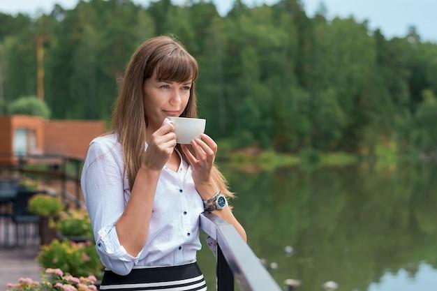 Jonge mooie vrouw in een zomerterras aan de rivier