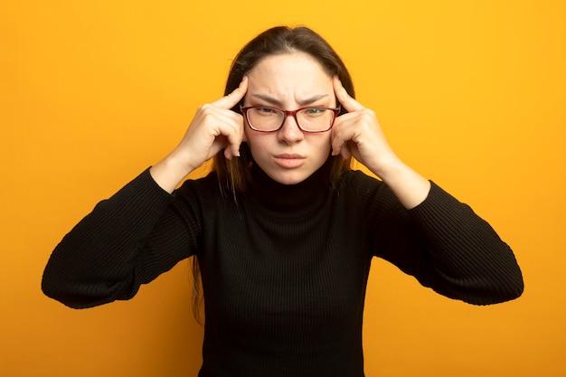 Jonge mooie vrouw in een zwarte coltrui die met vingers haar slapen richt met sterke hoofdpijn die zich over oranje muur bevindt