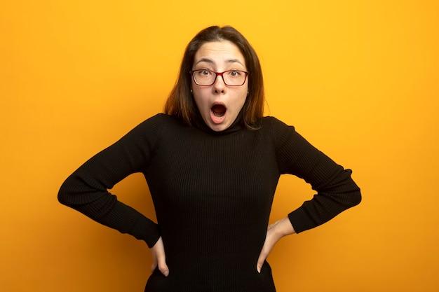 Jonge mooie vrouw in een zwarte coltrui die voorzijde bekijkt die zich verbaast en verrast bevindt zich over oranje muur