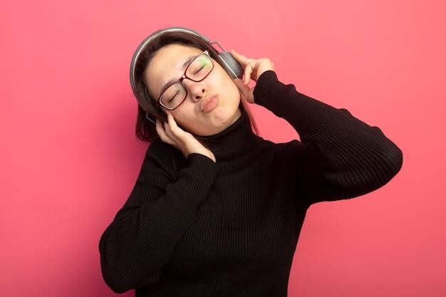 Jonge mooie vrouw in een zwarte coltrui en bril met koptelefoon genieten van haar favoriete muziek met gesloten ogen staande over roze muur