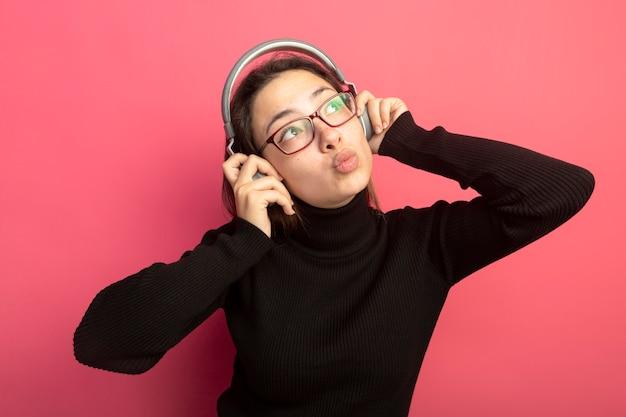 Jonge mooie vrouw in een zwarte coltrui en bril met koptelefoon kijken blij en positief staande over roze muur