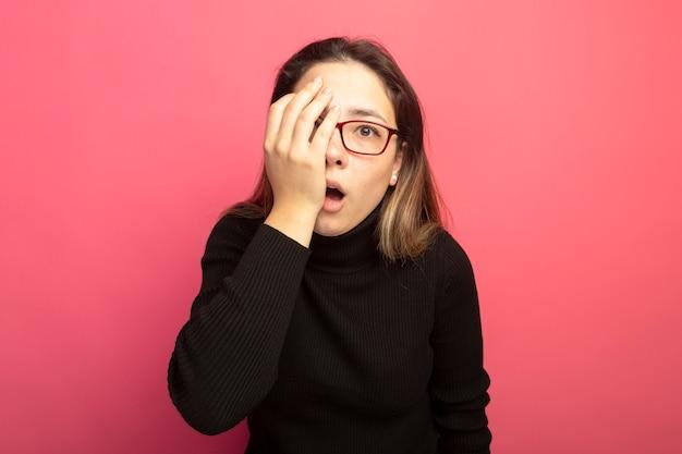 Jonge mooie vrouw in een zwarte coltrui en een bril die verward camera bekijkt en één oog bedekt met hand die zich over roze muur bevindt