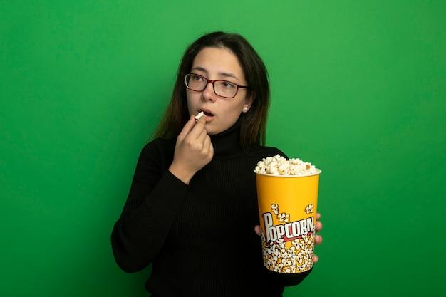 Jonge mooie vrouw in een zwarte coltrui en glazen die emmer met popcorn houden die popcorn eten die opzij kijken met gelukkige en posiitve status over groene muur