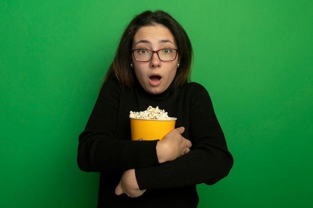 Jonge mooie vrouw in een zwarte coltrui en glazen die emmer met popcorn houden die voorzijde met vreesuitdrukking bekijken die zich over groene muur bevindt