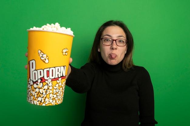 Jonge mooie vrouw in een zwarte coltrui en glazen die emmer met popcorn tonen die voorzijde uitsteekt tong bekijken die zich over groene muur bevindt
