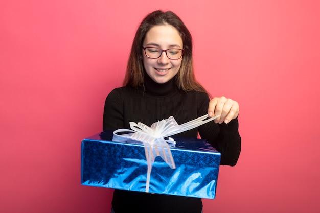 Jonge mooie vrouw in een zwarte coltrui en glazen die geschenkdoos houden die ernaar kijken met een blij gezicht dat zich over roze muur bevindt