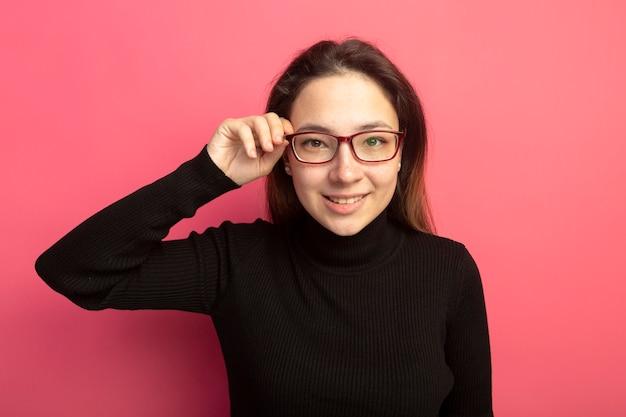 Jonge mooie vrouw in een zwarte coltrui en glazen die voorzijde met glimlach op gezicht bekijken die zich over roze muur bevinden