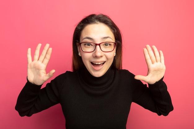 Jonge mooie vrouw in een zwarte coltrui en glazen die voorzijde met opgeheven handen bekijken die zich over roze muur bevinden