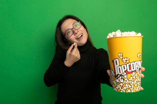 Jonge mooie vrouw in een zwarte coltrui en glazen met emmer met popcorn opzoeken met blij gezicht staande over groene muur