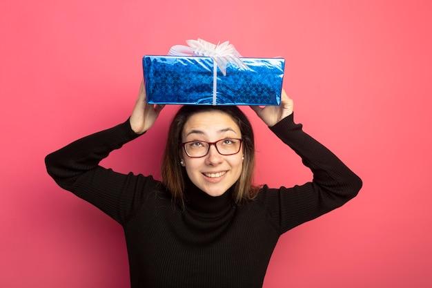 Jonge mooie vrouw in een zwarte coltrui en glazen met geschenkdoos boven haar hoofd lachend met blij gezicht staande over roze muur