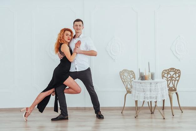 Jonge mooie vrouw in een zwarte jurk en een man in wit overhemd dansen.