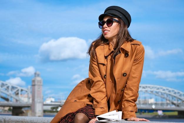 Jonge mooie vrouw in een zwarte pet en zonnebril in een jas aan de kade poseren met een krant in haar hand