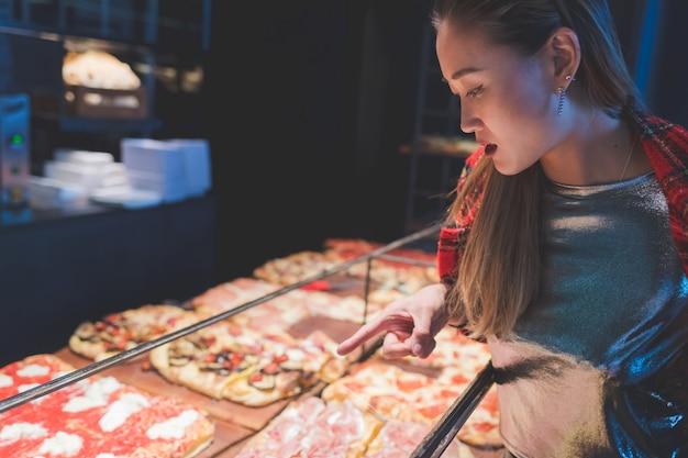 Jonge mooie vrouw in geruit overhemd die een pizzaplak kopen