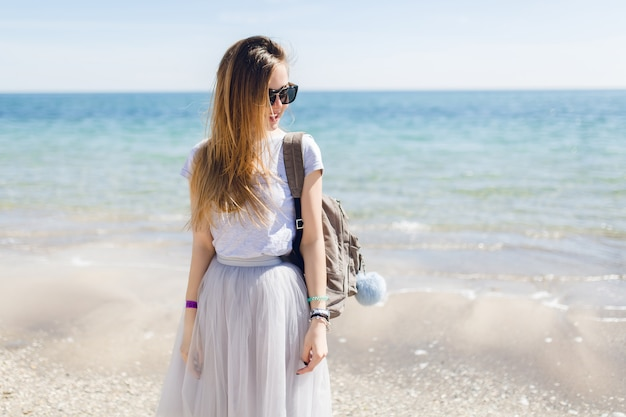 Jonge mooie vrouw in grijs t-shirt en weelderige rok staat in de buurt van zee