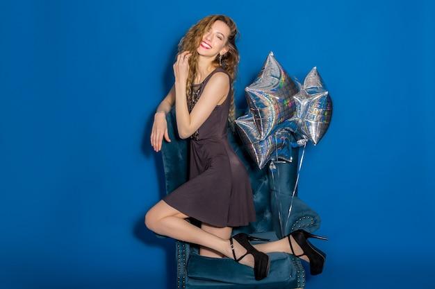 Jonge mooie vrouw in grijze jurk zittend op een blauwe fauteuil met zilveren ballonnen