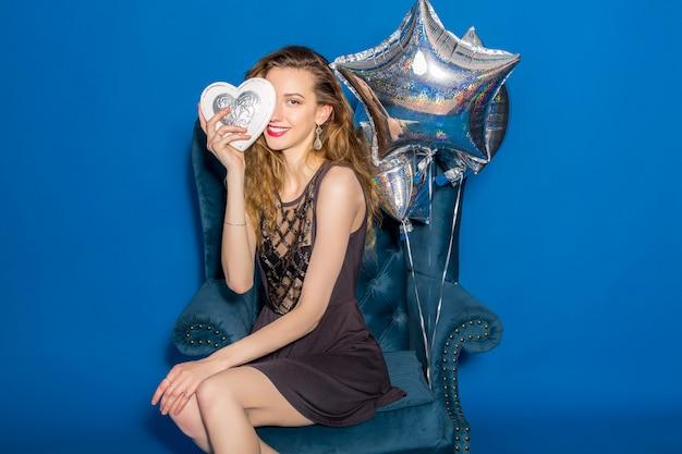 Jonge mooie vrouw in grijze jurk zittend op een blauwe fauteuil met zilveren hart