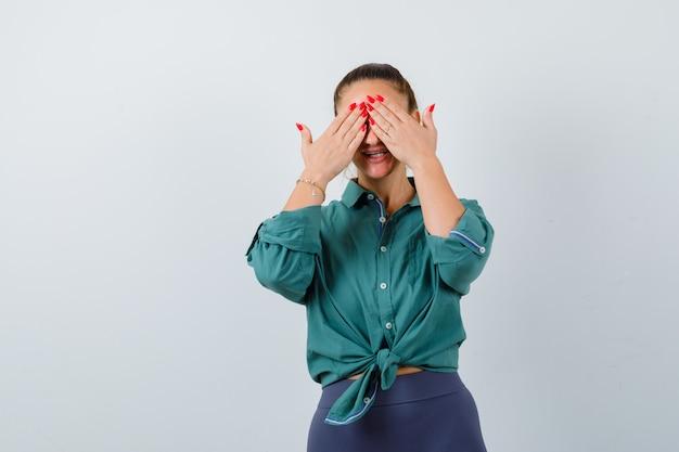 Jonge mooie vrouw in groen shirt die ogen bedekt met handen en er blij uitziet, vooraanzicht.