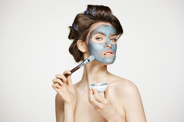 Jonge mooie vrouw in haarkrulspelden die gezicht behandelen met mack. gezichtsbehandeling. schoonheid cosmetologie en spa.