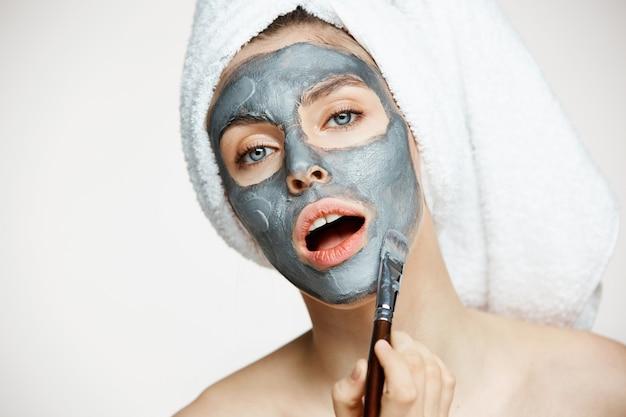 Jonge mooie vrouw in handdoek op hoofd bedekkend gezicht met masker met geopende mond. schoonheid cosmetologie en spa.