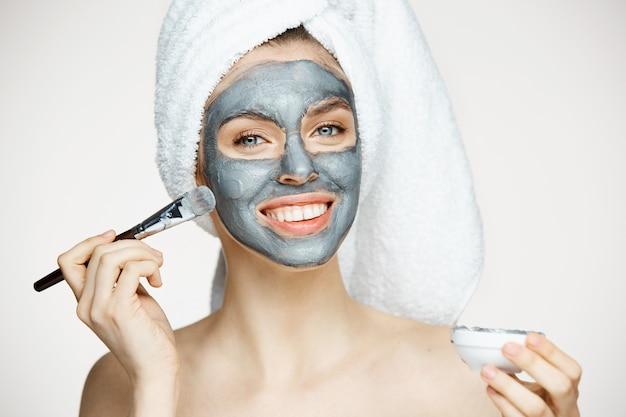 Jonge mooie vrouw in handdoek op hoofd die gezicht behandelen met masker het glimlachen. schoonheid cosmetologie en spa.