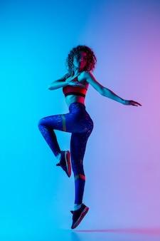 Jonge mooie vrouw in heldere sportwear die op roze-blauwe achtergrond met kleurovergang in neonlicht wordt geïsoleerd.