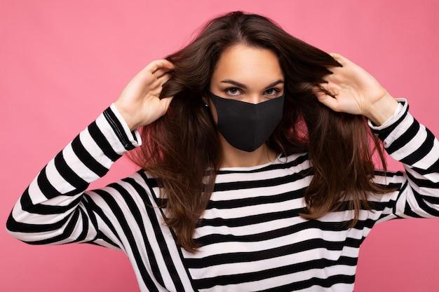 Jonge mooie vrouw in herbruikbaar virusbeschermend masker op gezicht tegen coronavirus geïsoleerd op de roze achtergrondmuur