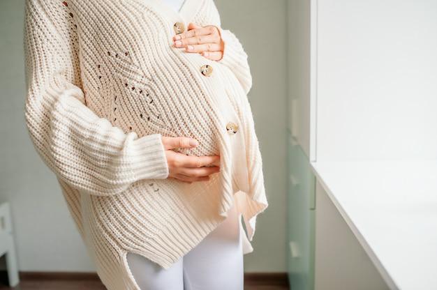 Jonge mooie vrouw in het derde trimester van de zwangerschap. bijgesneden schot van zwangere vrouw in gebreide trui met handen op buik