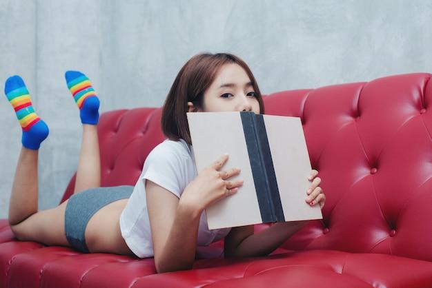 Jonge mooie vrouw in het leesboek van de witte lingerie in de bedrest, comfort