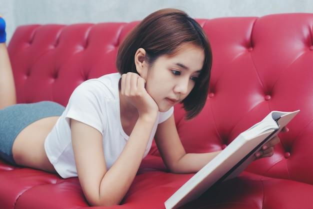Jonge mooie vrouw in het leesboek van de witte lingerie in de bedrest