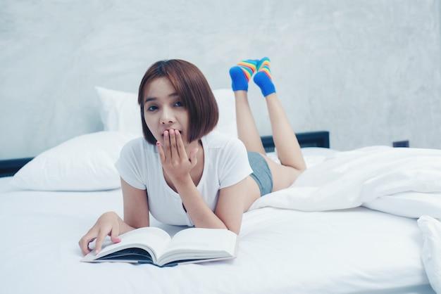 Jonge mooie vrouw in het leesboek van de witte lingerie in het bed