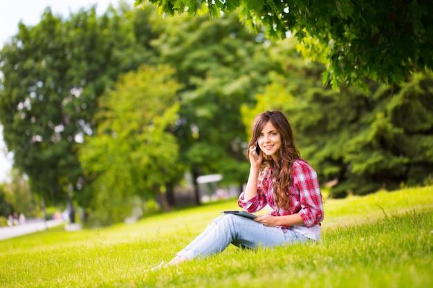 Jonge mooie vrouw in het park met gadgets