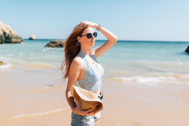 Jonge mooie vrouw in hoed op het strand bij oceaan