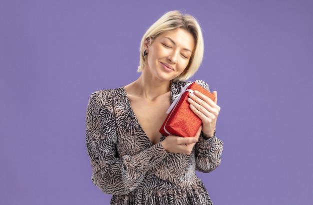 Jonge mooie vrouw in jurk bedrijf aanwezig lachend met gesloten ogen gevoel dankbaar valentijnsdag concept staande over paarse muur