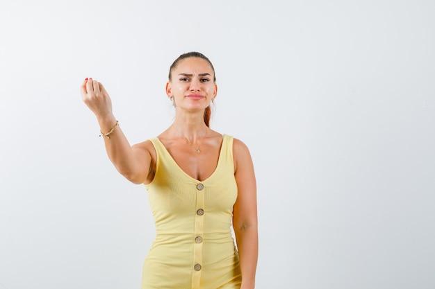 Jonge mooie vrouw in jurk italiaanse gebaar tonen en op zoek boos, vooraanzicht.