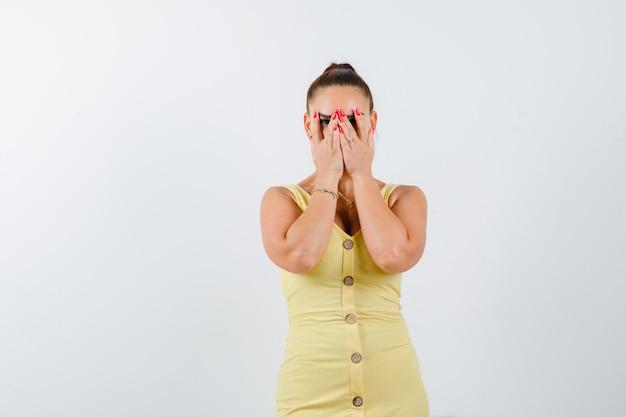 Jonge mooie vrouw in jurk kijkt door de vingers en kijkt nieuwsgierig, vooraanzicht.