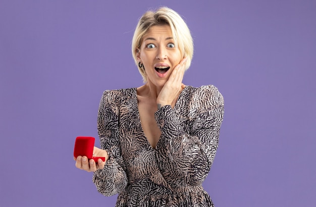 Jonge mooie vrouw in jurk met rode doos met verlovingsring camera kijken blij en verrast valentijnsdag concept staande over paarse muur