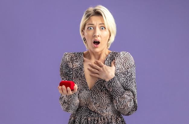 Jonge mooie vrouw in jurk met rode doos met verlovingsring camera kijken verbaasd en geschokt valentijnsdag concept staande over paarse muur