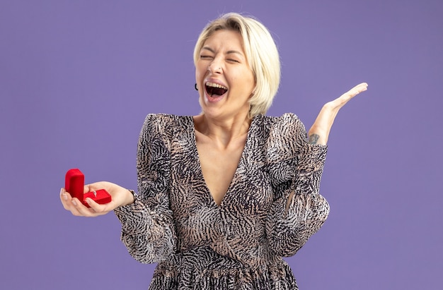 Jonge mooie vrouw in jurk met rode doos met verlovingsring schreeuwen blij en opgewonden valentijnsdag concept staande over paarse muur