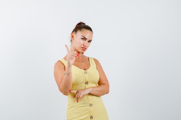 Jonge mooie vrouw in jurk waarschuwing met vinger en op zoek woedend, vooraanzicht.