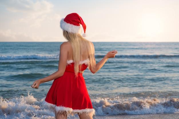 Jonge mooie vrouw in kerstmankostuum viert kerstmis op een reis naar warme landen op het zandstrand van de zee