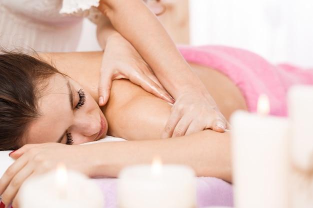 Jonge mooie vrouw in kuuroordsalon die lichaams ontspannende massage heeft